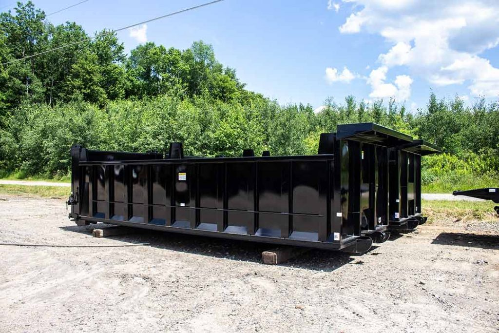 Black dump body roll-off container with board pockets, cab shield, and dump style tailgate