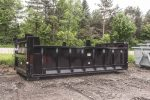 Black dump body roll-off contianer with dirt shedders and hooklift style hookup