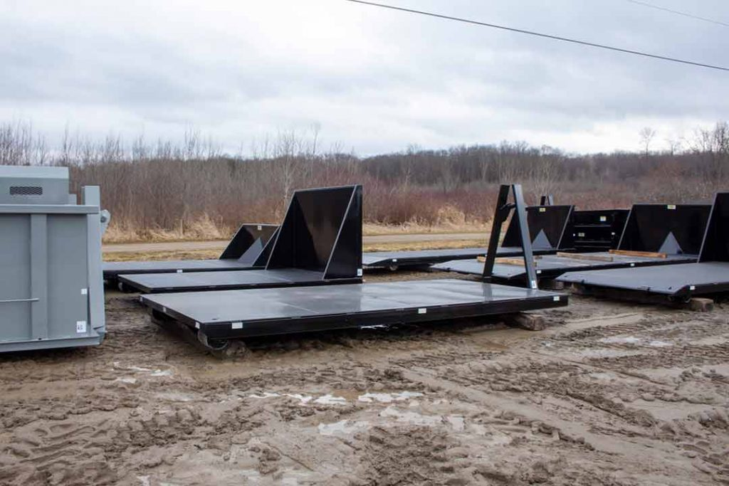 A variety of styles of black flatbed roll-off containers