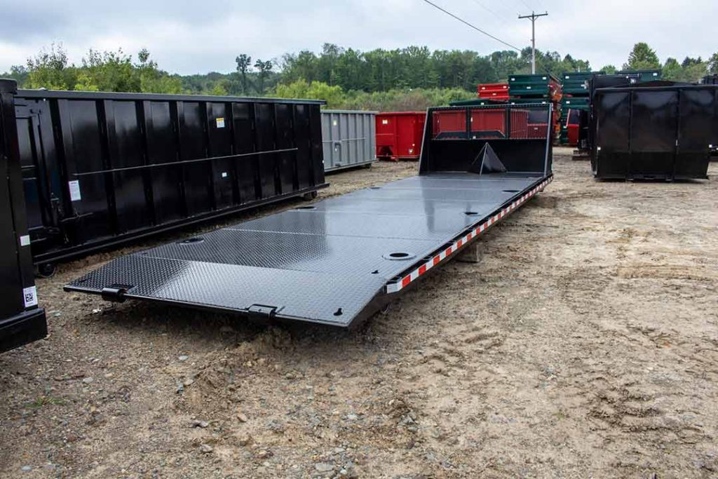 Black flatbed roll-off container with expanded metal bulkhead, beavertail, recessed D-Rings, DOT reflective tape and cable hookup