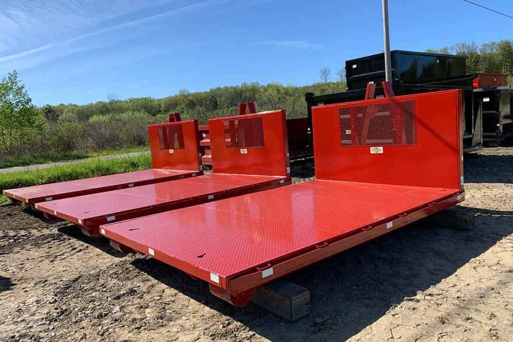 Red flatbed roll-off container with expanded metal bulkhead window and hooklift hookup