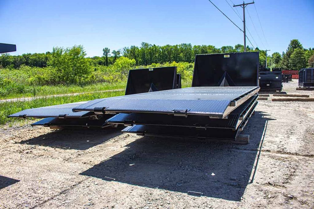 Standard Bucks Fabricating Flatbed roll-off containers kept in stock with cable hookup and beavertail