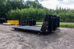 Two black flatbed roll-off containers with hooklift hookups.
