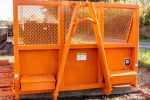 Orange flatbed roll-off container with expanded metal bulkhead window and hooklift hookup