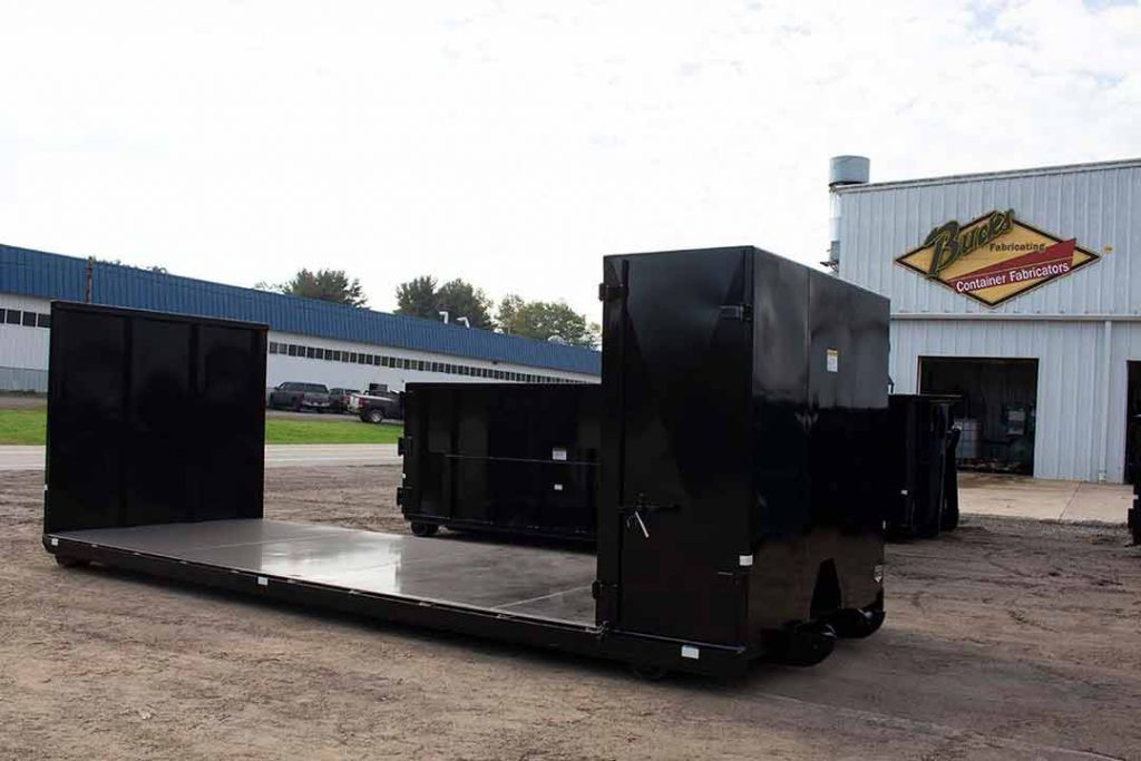 Black flatbed roll-off container with double bulkhead, one bulkhead with toolbox, and cable style hookup