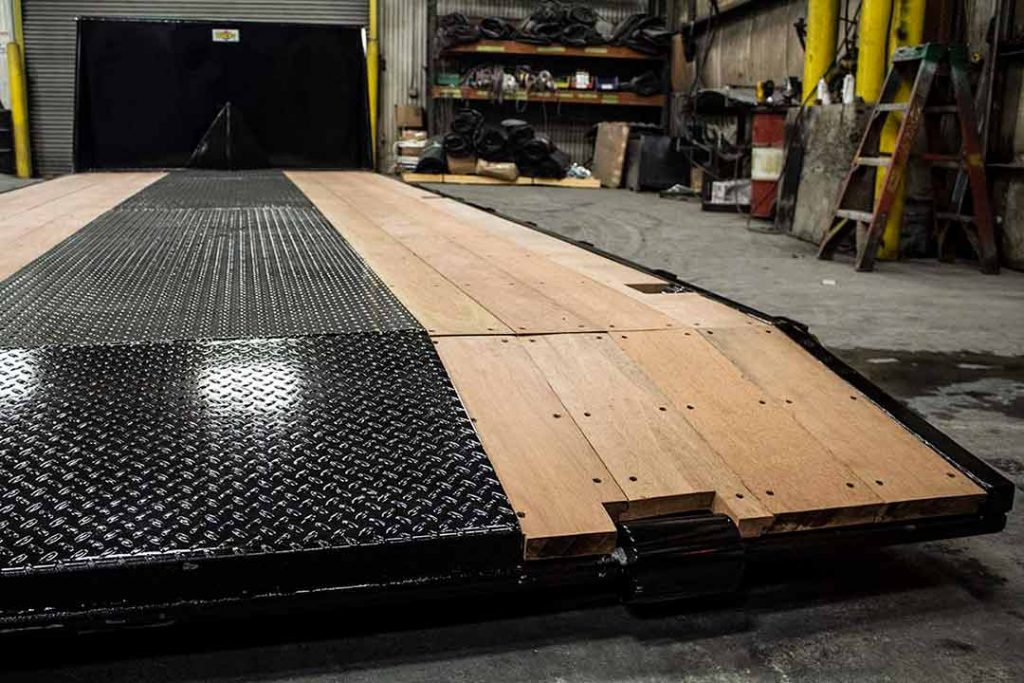 Black flatbed roll-off container with apitong tracking and beavertail