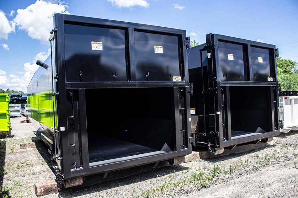 Two black Octagon Packers, or compactor receivers in black with liner hooks and rectangular openings