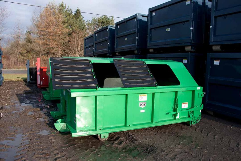 Green recycler style roll off container with peak style roof, open hinged lids, and cable style hookup