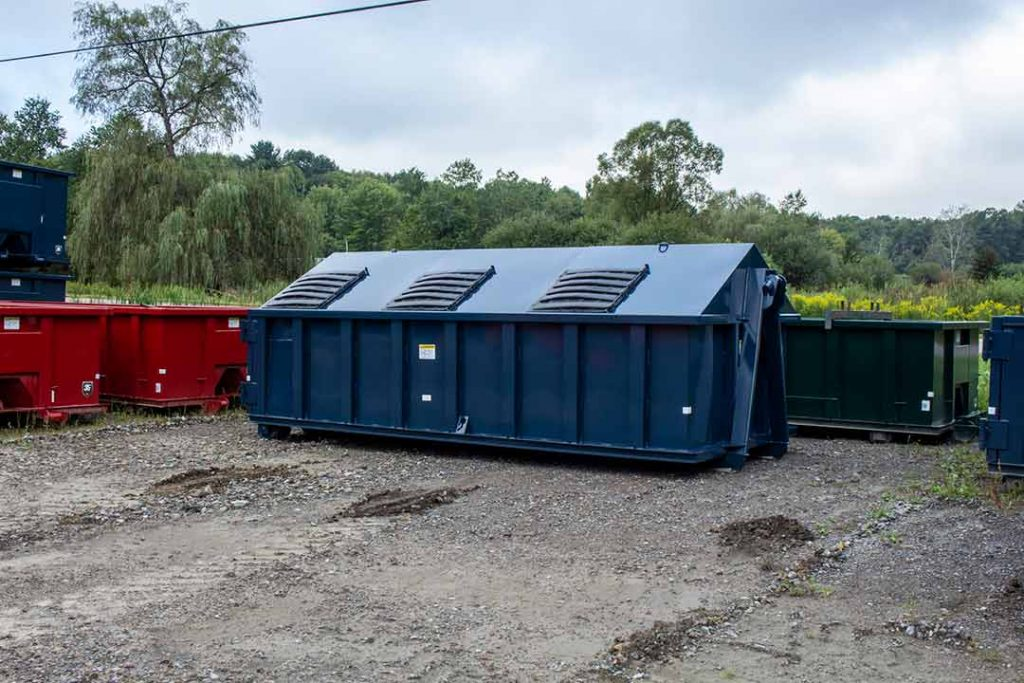 Blue recycler style roll off container with peak style roof, hinged lids, and hooklift style hookup
