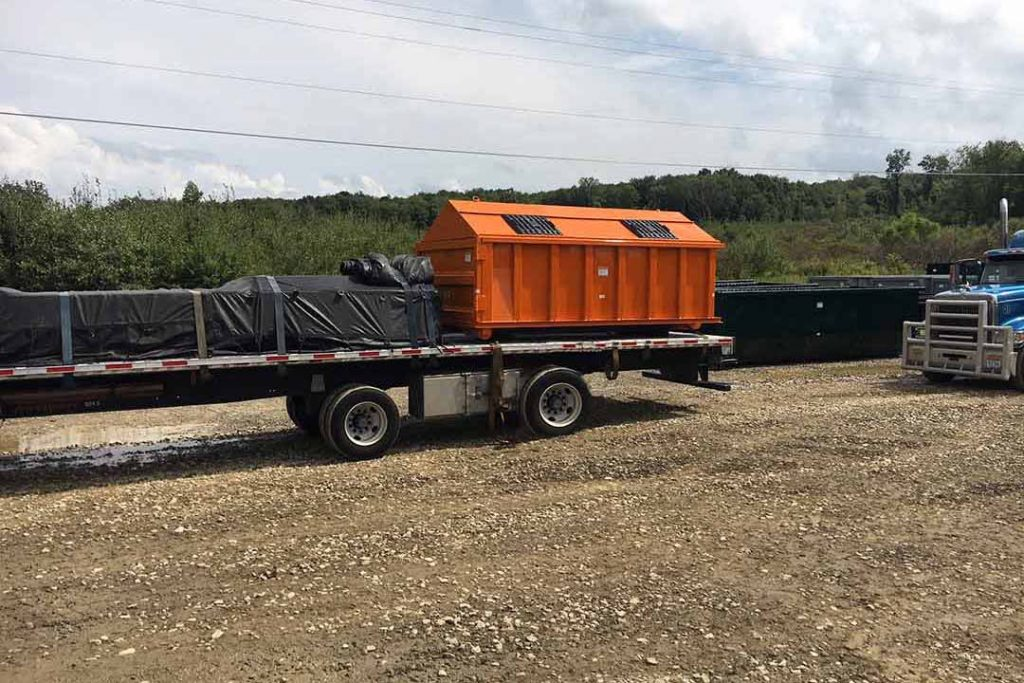 Orange recycler style roll off container with peak style roof, sliding lids, and cable style hookup on a truck deck