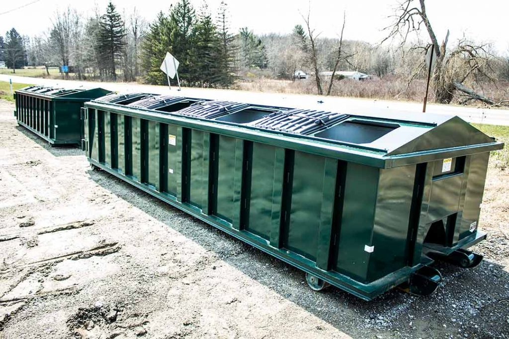 Green recycler style roll off container with peak style roof, open sliding lids, and cable style hookup