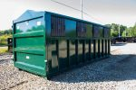 Green recycler style roll off container with peak style roof, sliding lids on side, and cable style hookup