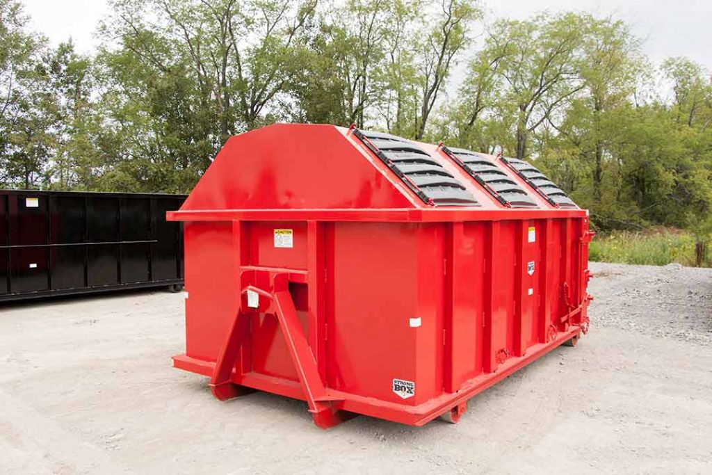 Red recycler style roll off container with gambrel style roof, sliding lids, and hooklift style hookup
