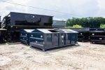 Blue recycler style roll off container with peak style roof, hinged lids, and hooklift style hookup with one lid open and one lid closed