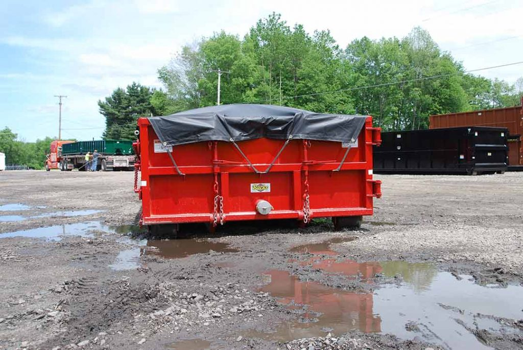 Red sealed style roll off container with side roll tarp system and single pipe and nipple cap on sealed tailgate