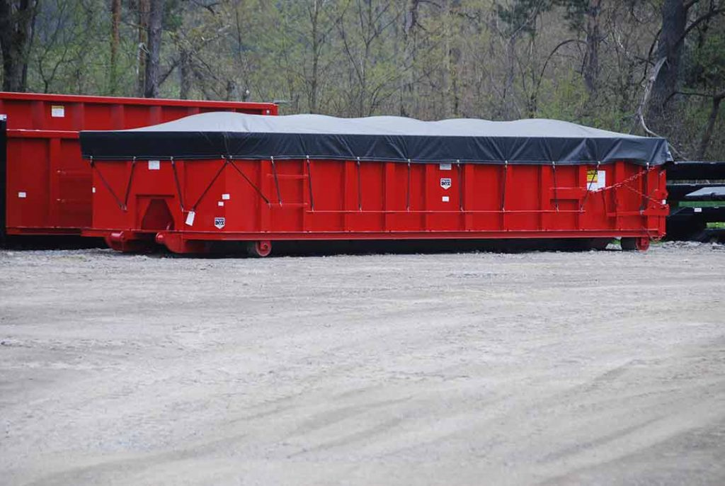 Red sealed style rolloff container with side roll tarp system and cable style hookup