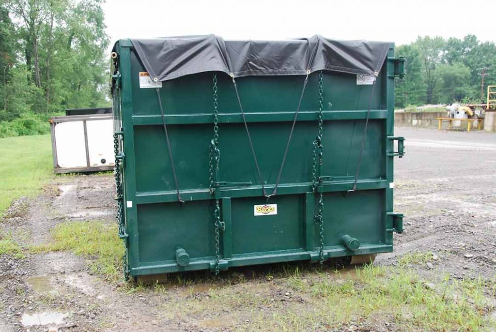 Green sealed style rolloff container with side roll tarp system with two pipe and nipple caps and two ratchet binders on sealed tailgate