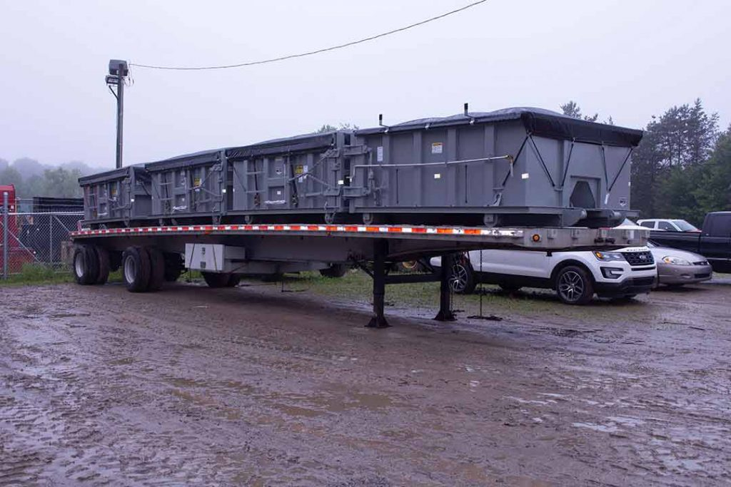 Gray sealed style rolloff containers with side roll tarp systems on truck deck getting ready to ship