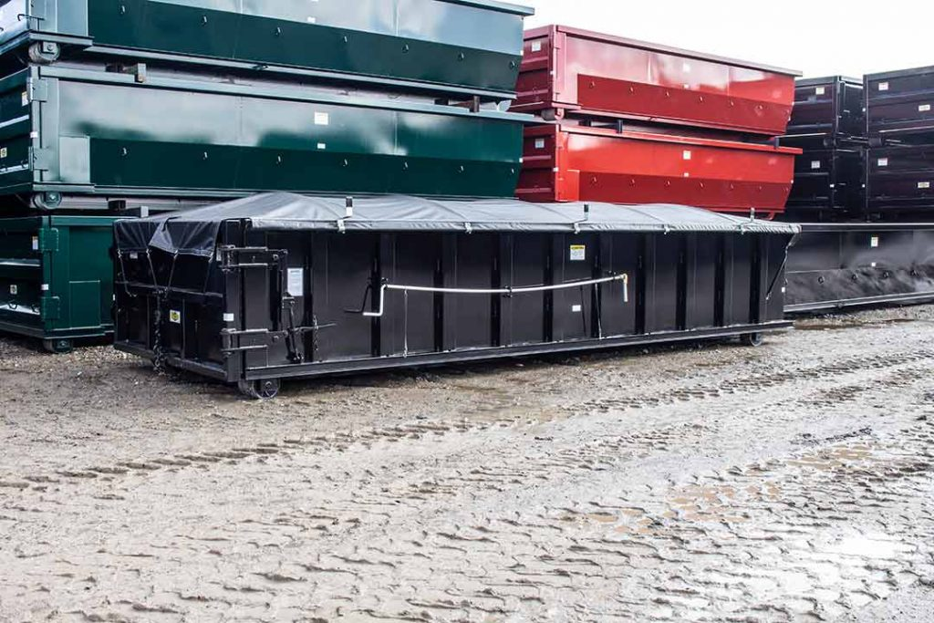 Black sealed style roll off container with side roll tarp system and cable hookup