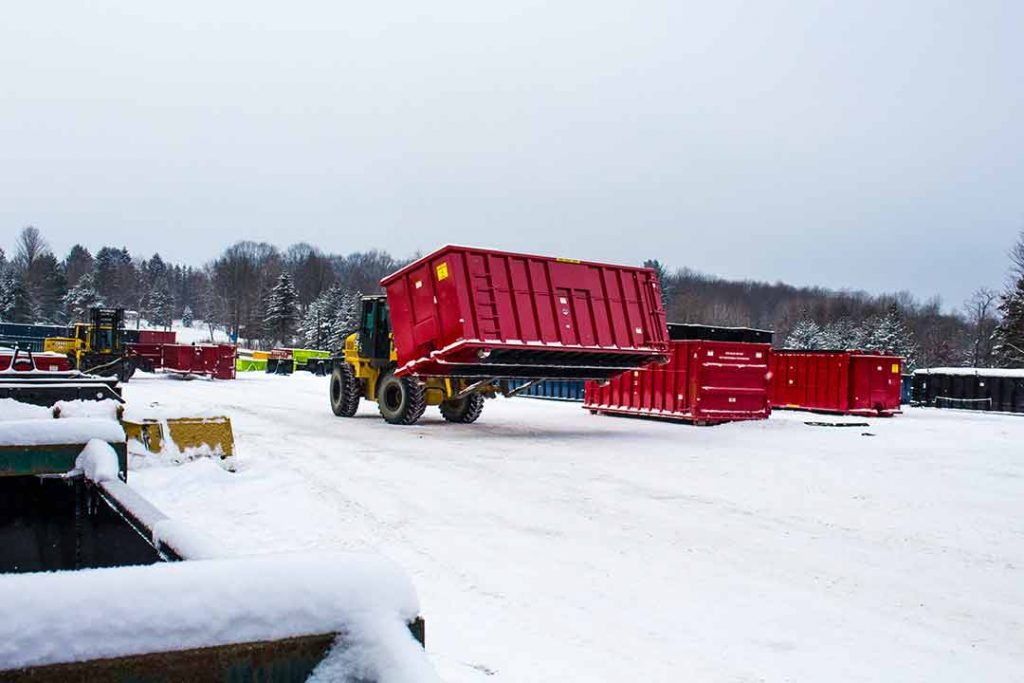 Red Strong Box rolloff container with sign plates and cable style hookup being carried across the yard by a fork truck