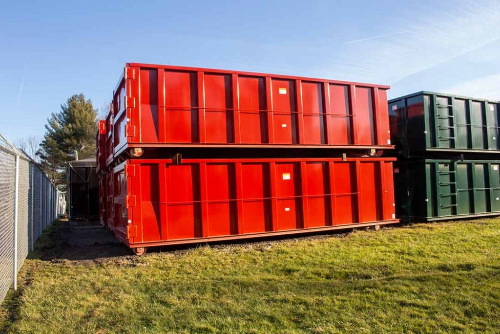 Red Tough Box rolloff containers with single side swing tailgate and cable style hookup stacked in the yard