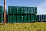 Green Tough Box rolloff containers with single side swing tailgate and cable style hookup stacked in the yard