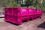Pink vacuum tank rolloff container with blind flange used to seal the pipe when not in use